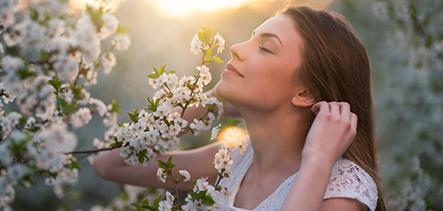 Mujer oliendo flores de la naturaleza
