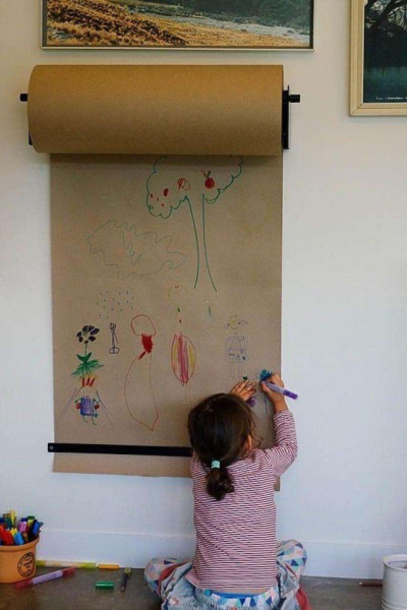 niña pintando en la pared en el papel kraft