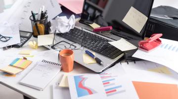 escritorio desordenado con papeles y otros objetos de oficina